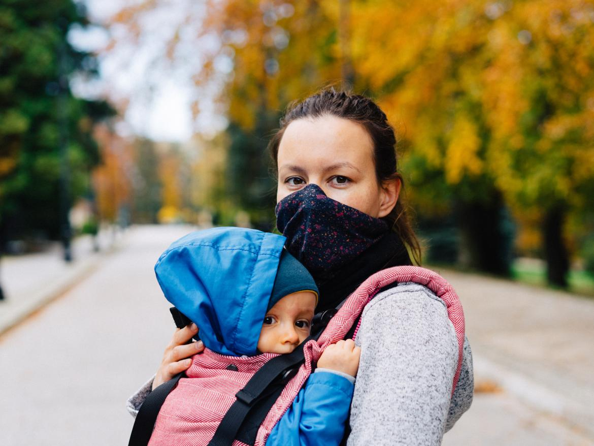 Mother wearing facemask walks with child.