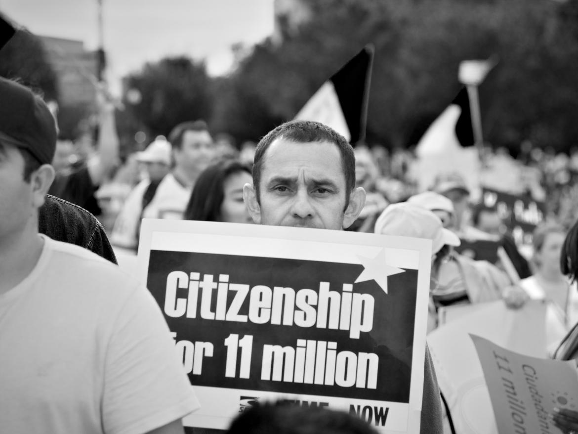 "Man holding sign at rally that says ""Citzenship for 11 Million"""