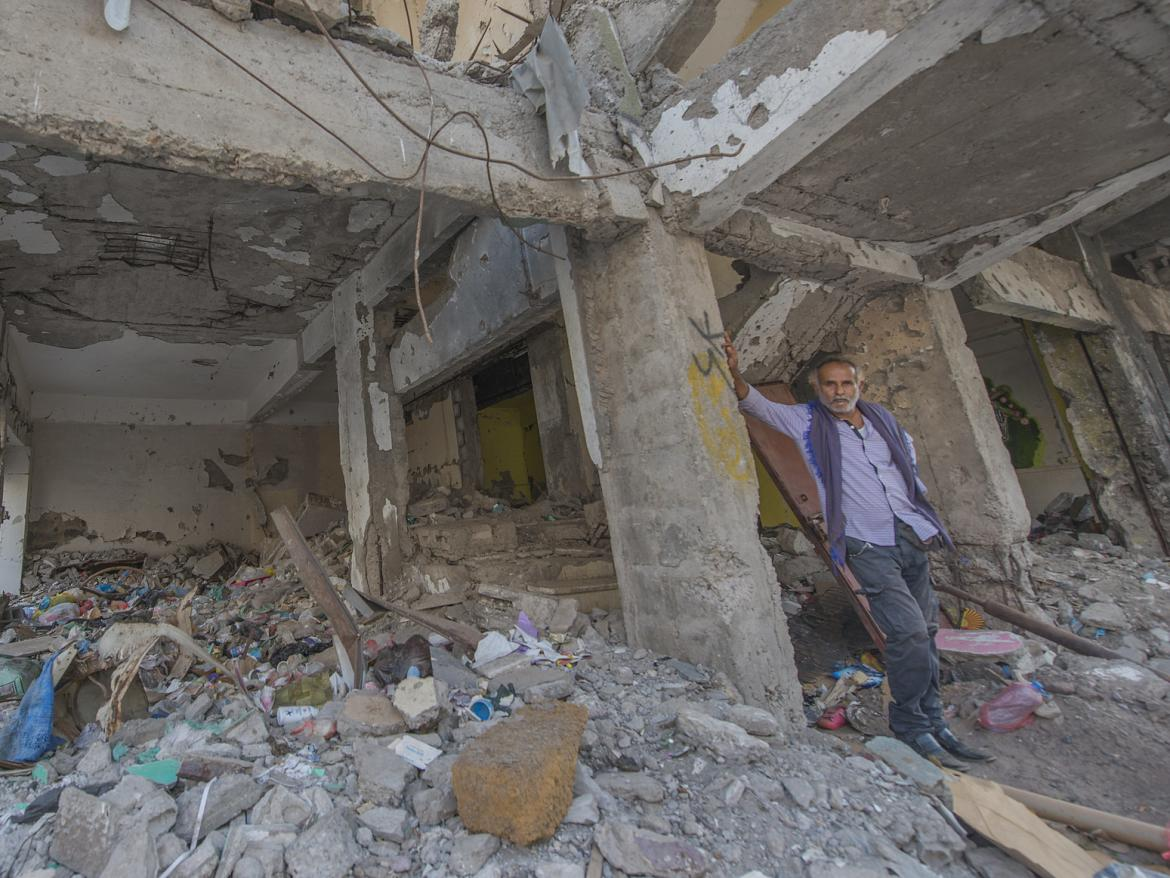 A man stands the rubble of a building destroyed in an air raid in a neighborhood in Aden, Yemen.