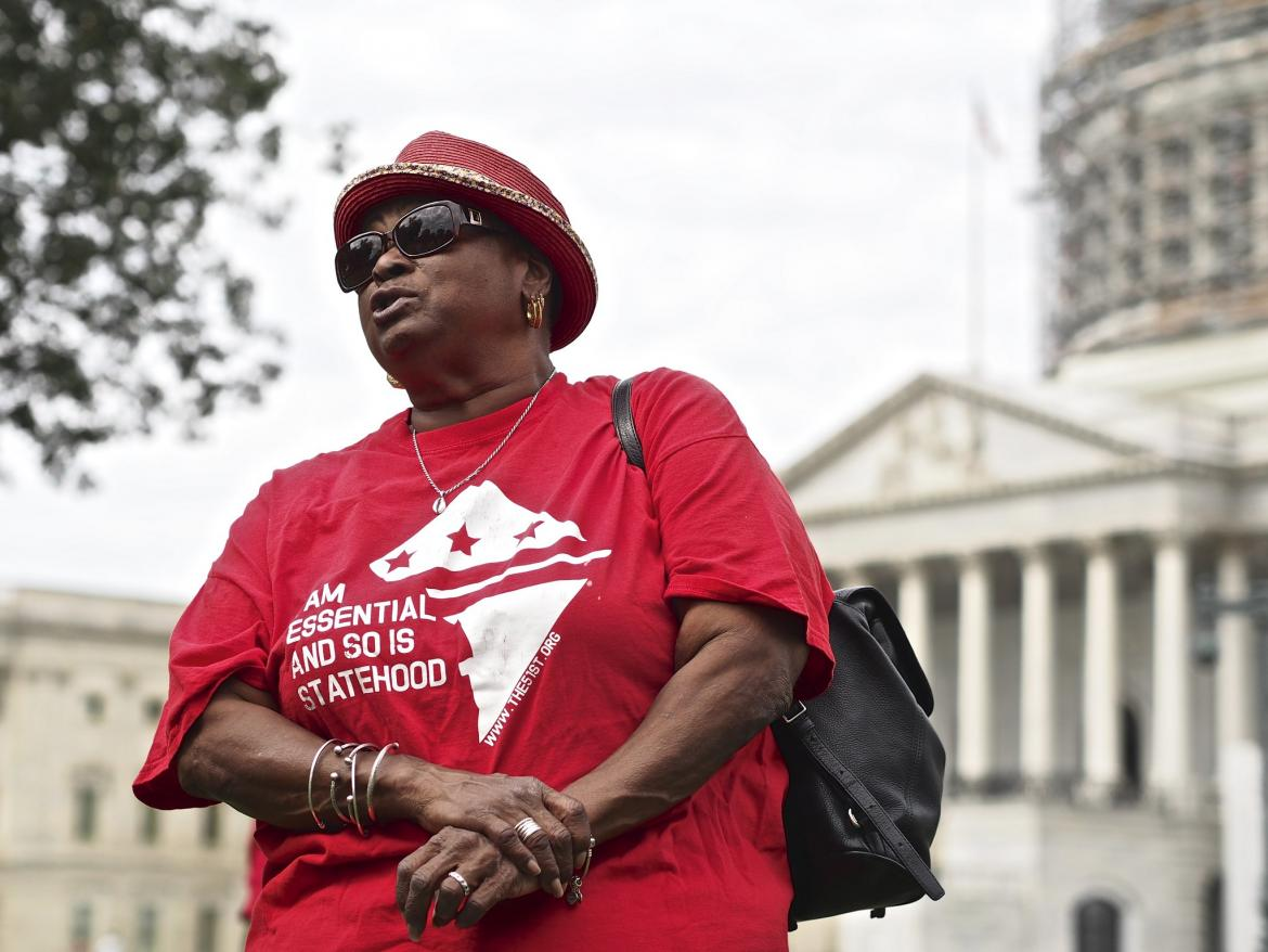 "A woman stands in front of the U.S. Capitol wearing a shrit that says "" I Am Essential and so Is Statehood """