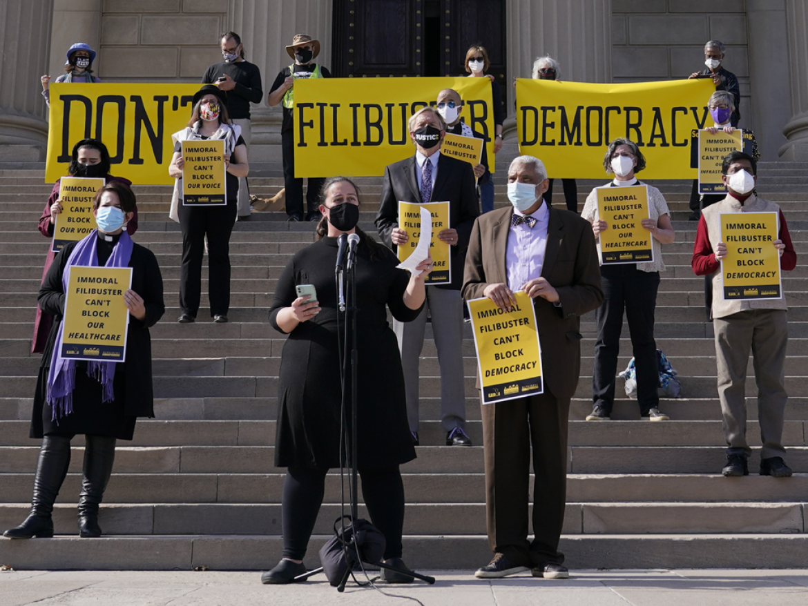 Rev. Liz Theoharis, center at microphone, co-director of The Poor People's Campaign, speak outside National City Christian Church in Washington, Monday, April 5, 2021.