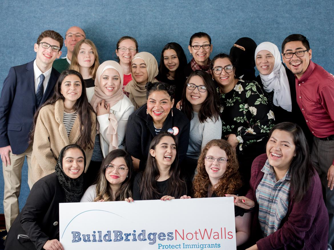 "Spring Lobby Weekend participants holding sign that says ""build bridges, not walls"""