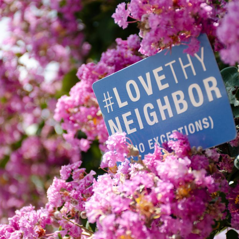 Love Thy Neighbor sign in flowering tree