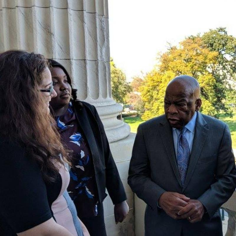 Five people meet with Rep. John Lewis in front of the Capitol