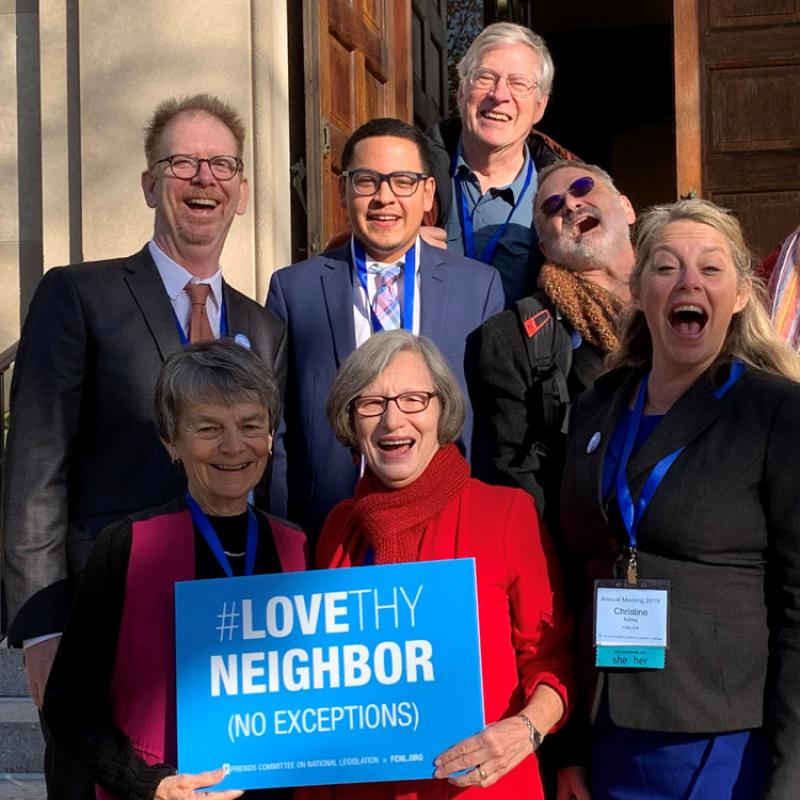 Group holding Love They Neighbor sign at annual meeting 2019