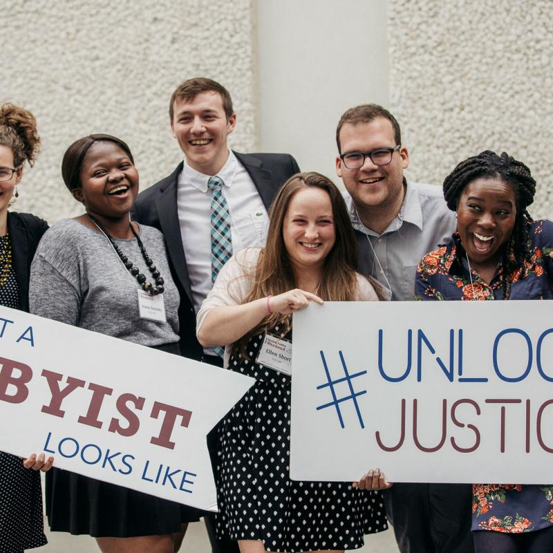 Young people hold signs that say This Is What a Lobbyist Looks Like and Unlock Justice.