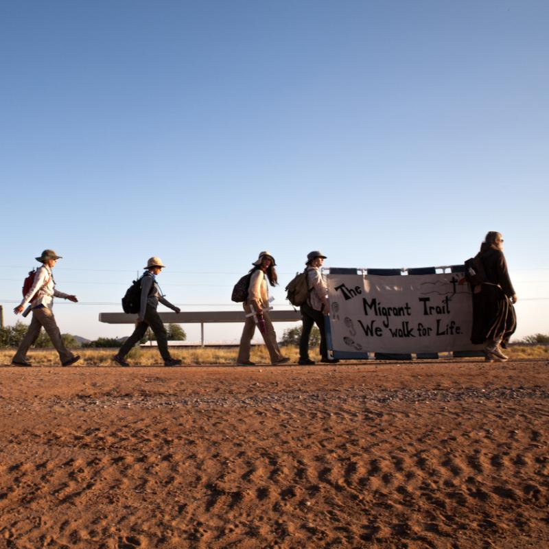 Group walks through desert with banner.